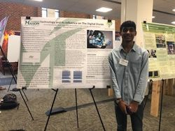 A student stands in front of their poster presentation