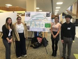 Four students stand in front of their shared poster presentation