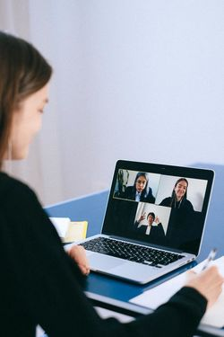 Woman sits before a video call with two other women, taking notes