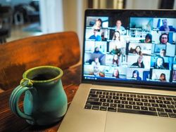 A blue mug sits to the left of a laptop which shows many speakers on a conference call.